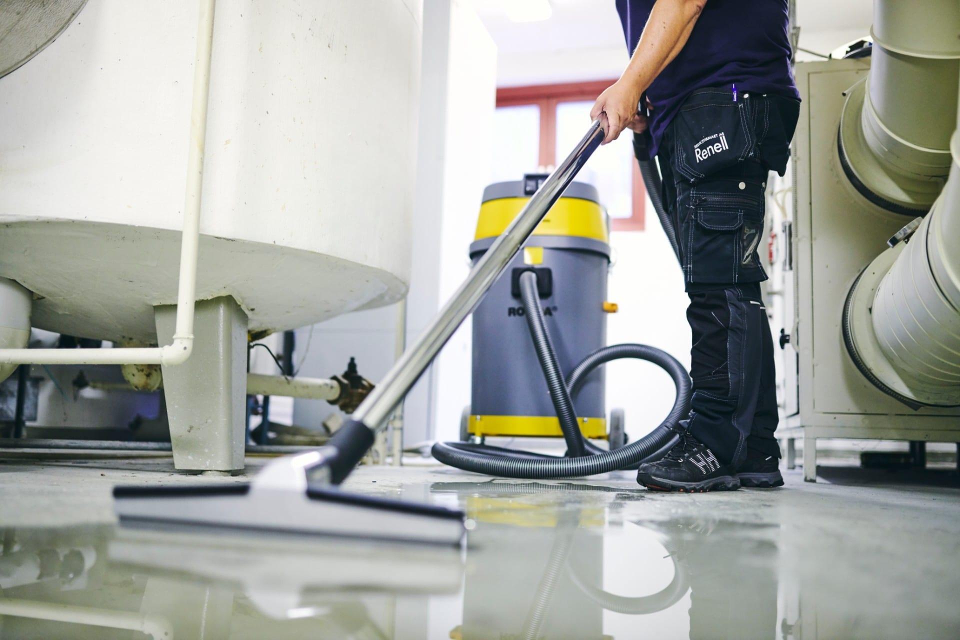 Renell-medarbejder bruger vandstøvsuger til at fjerne vand fra kældergulv
