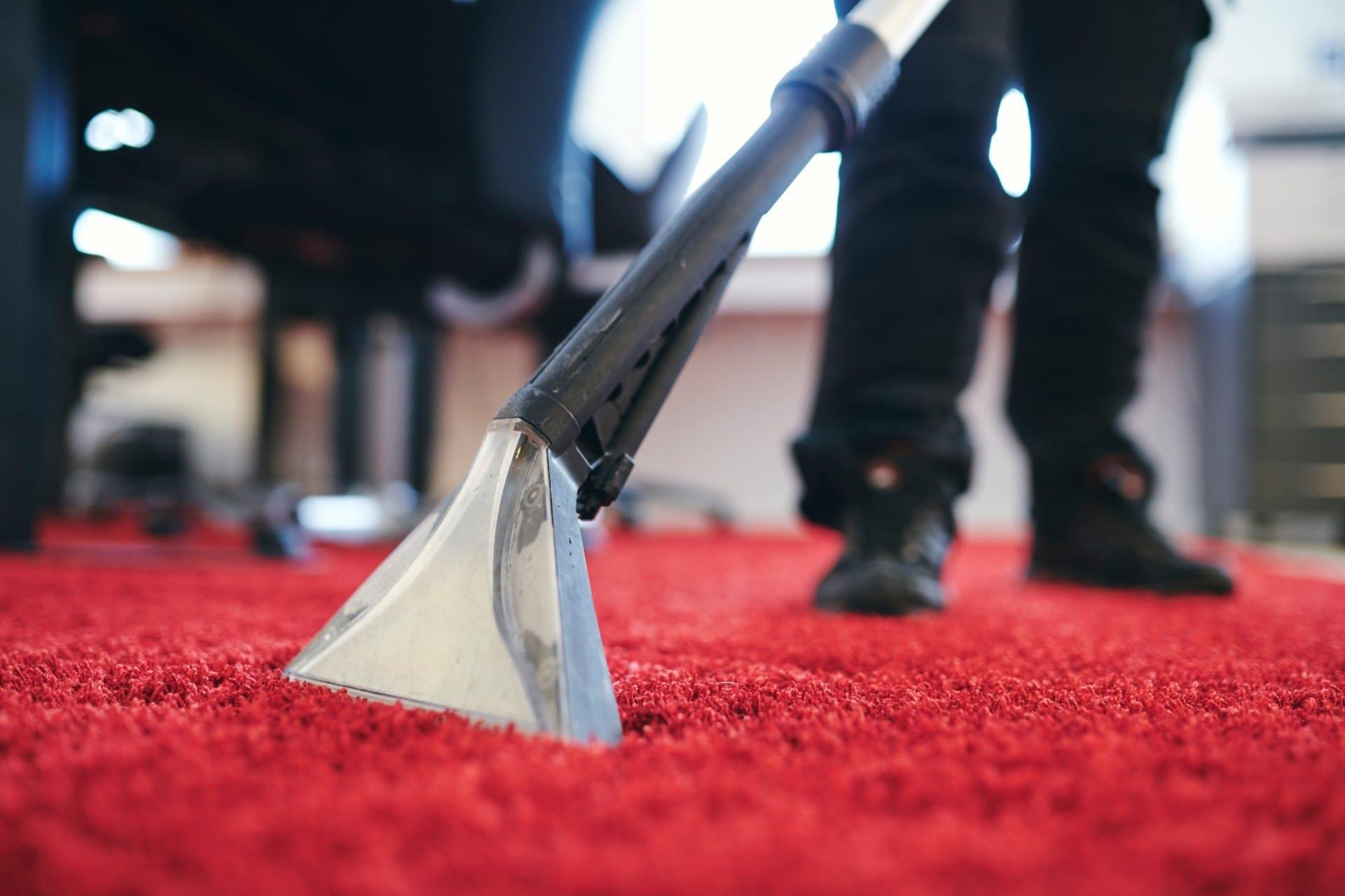 Renell-medarbejder støvsuger og renser et gulvtæppe