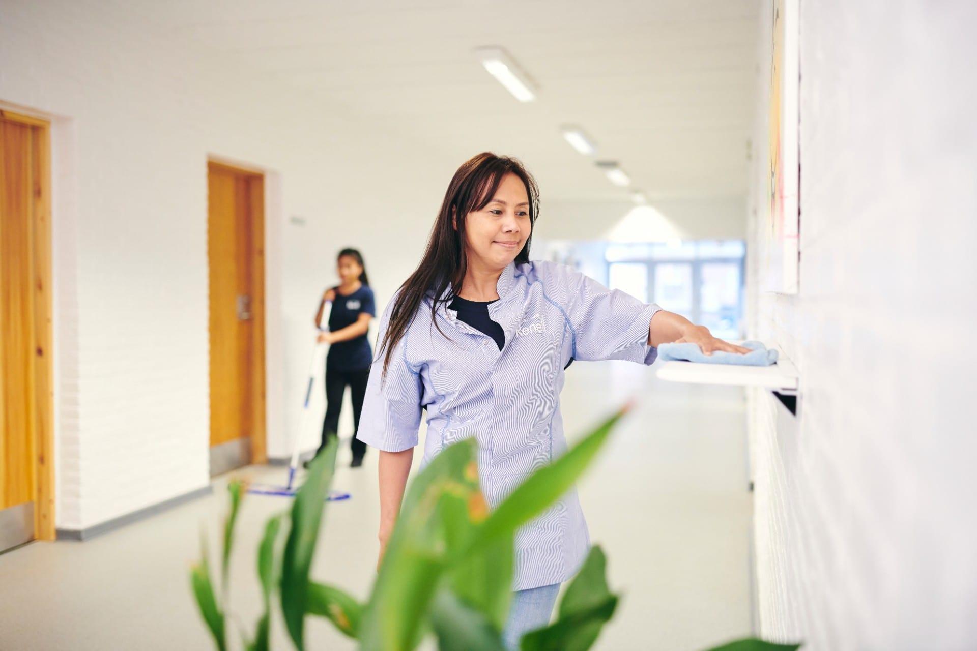 Renell-medarbejdere vasker gulv og tørrer flader af på skole-gang