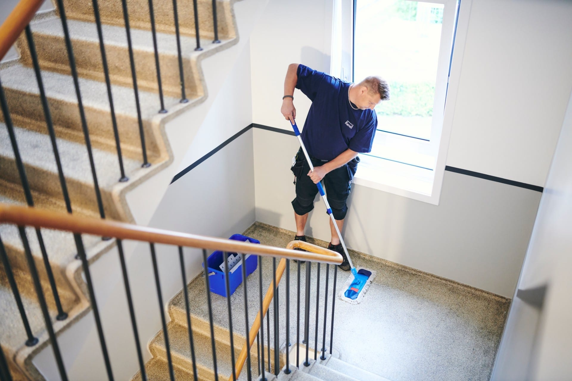 Renell-medarbejder vasker gulv i trappeopgang
