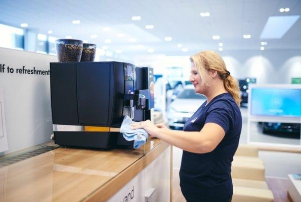 Renell-medarbejder tørrer kaffemaskine af hos erhvervskunde