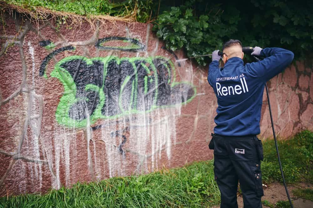 Renell-medarbejder fjerner grafitti fra mur