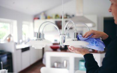 Renell-medarbejder tørrer støv af på lampe i privathjem