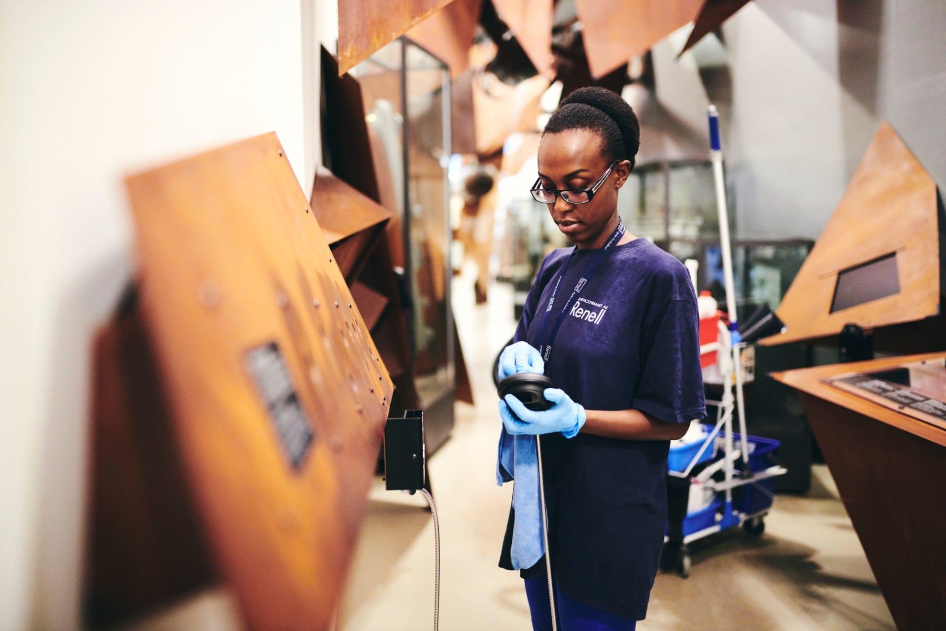 Renell-medarbejder tørrer høretelefoner af på et museum