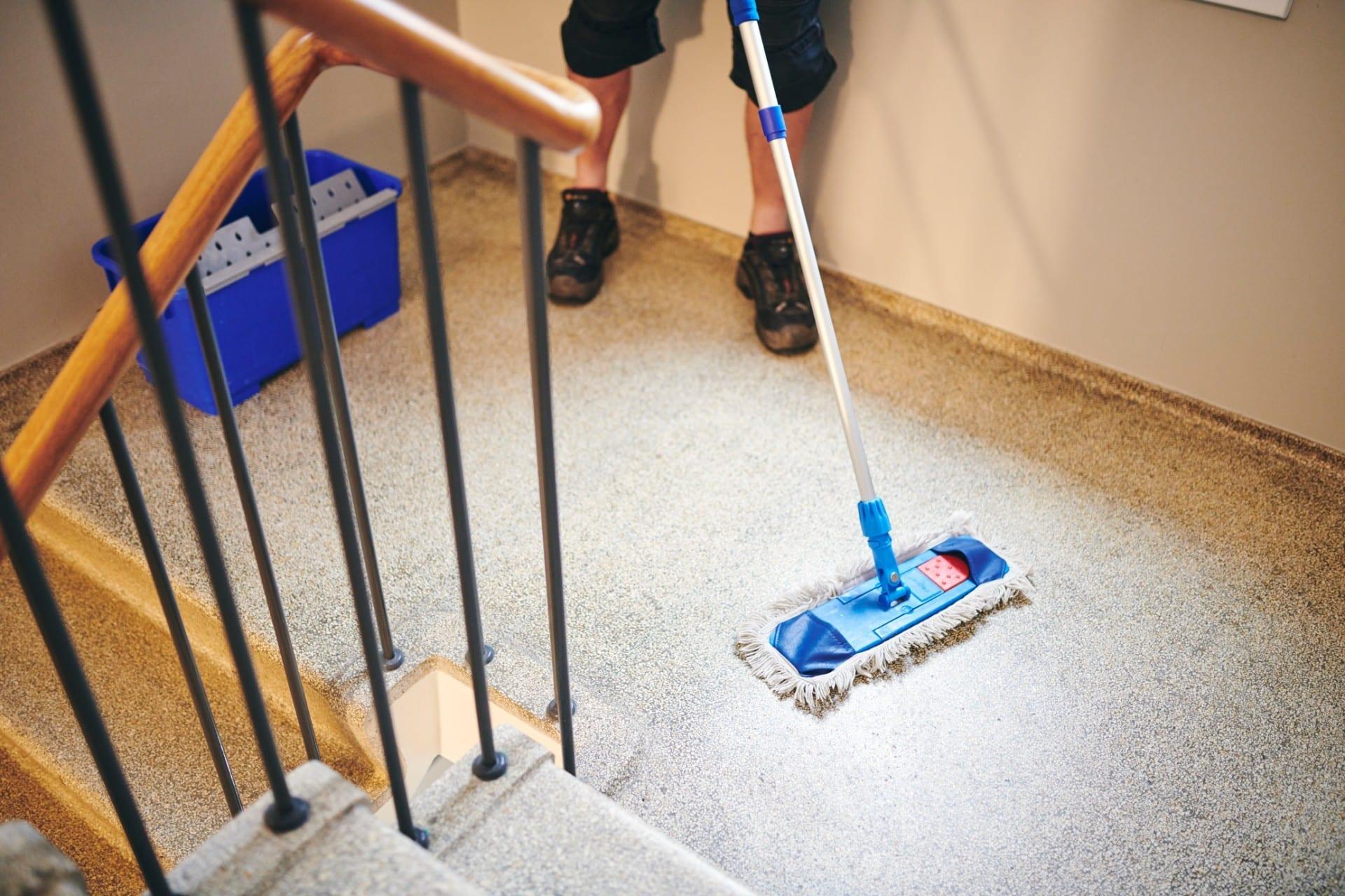 Renell-medarbejder vasker gulvet i trappeopgang