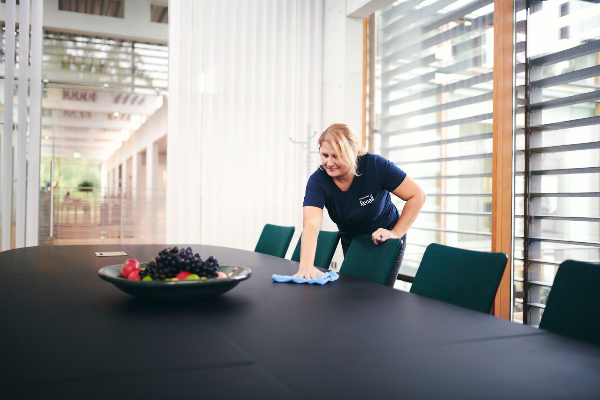 Renell-medarbejder tørrer bord af i mødelokale hos en erhvervskunde
