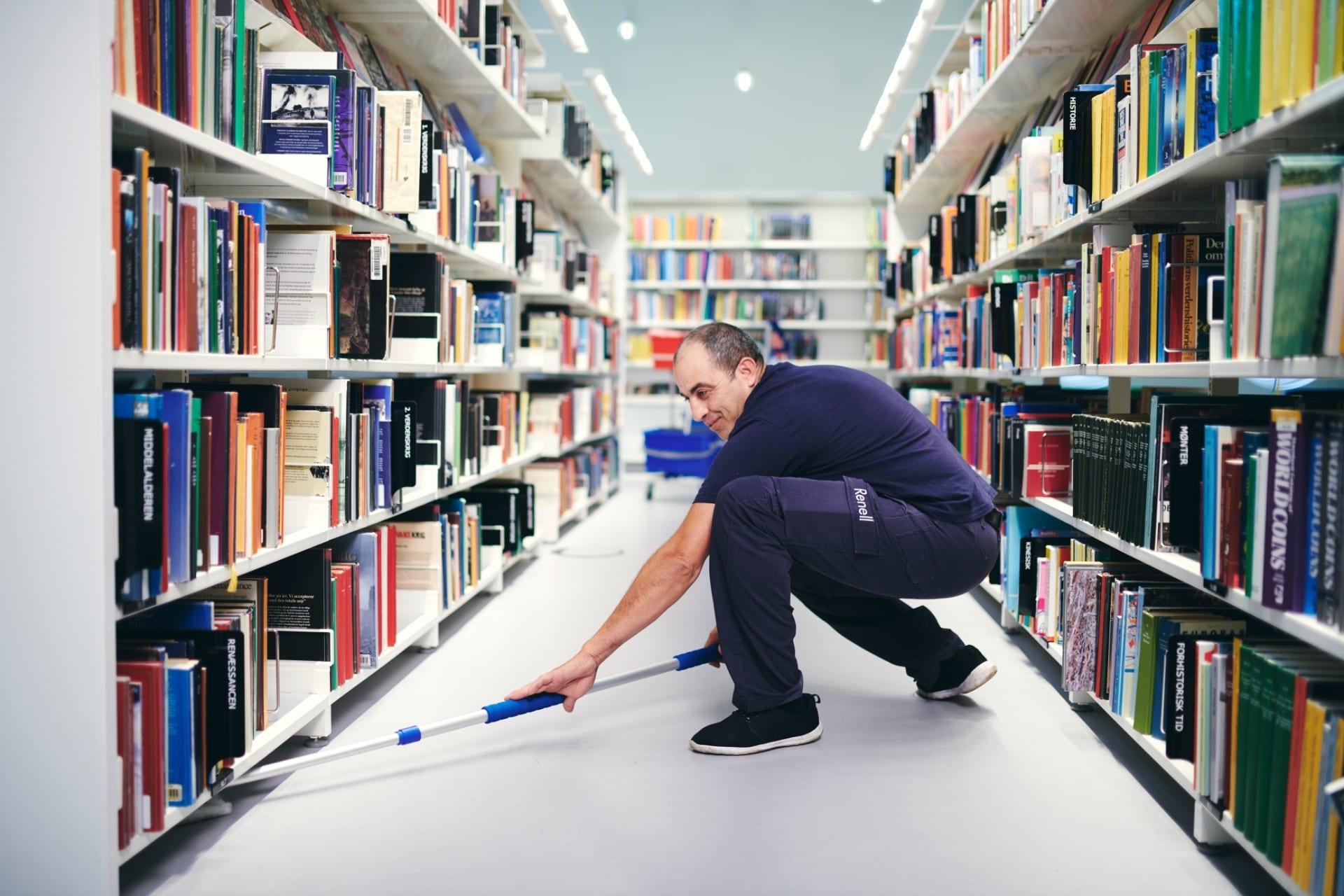 Renell-medarbejder fejer gulv på bibliotek