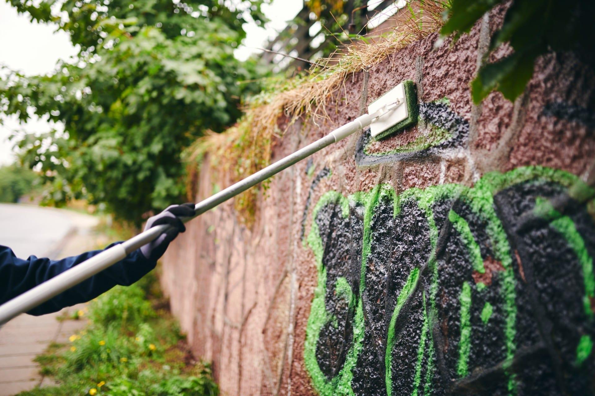 Renell-medarbejder fjerner grafitti på mur