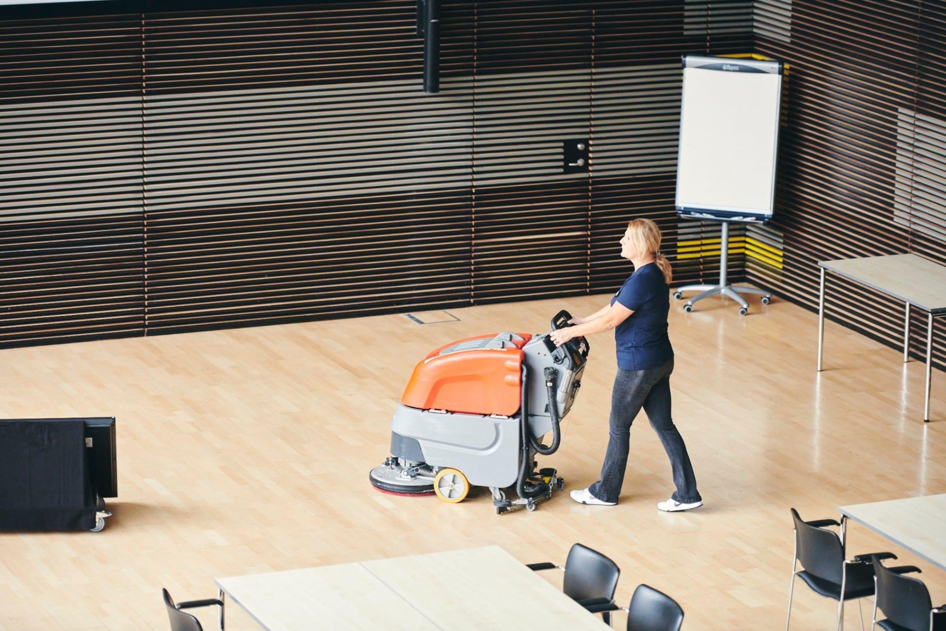 Renell-medarbejder vasker gulv hos erhvervskunde med gulvmaskine
