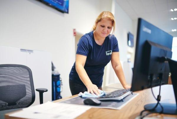 Renell-medarbejder aftørrer skrivebord på arbejdsplads